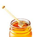 Miel en un tarro de cristal con el cazo de la miel aislado en el backgr blanco Imagen de archivo libre de regalías