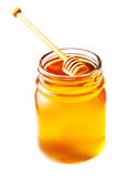 Miel en un tarro de cristal con el cazo de la miel aislado en el backgr blanco Fotos de archivo libres de regalías