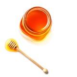 Miel en un tarro de cristal con el cazo de la miel aislado en el backgro blanco Imagen de archivo