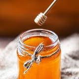 Miel en un tarro de cristal con el cazo de la miel en backgro de madera del vintage Imágenes de archivo libres de regalías