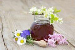 Miel en un tarro, flores y cazo de la miel Fotografía de archivo