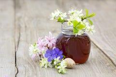 Miel en un tarro, flores y cazo de la miel Imágenes de archivo libres de regalías