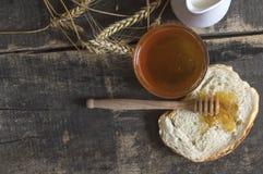 Miel en un tarro, un pan, un trigo y una leche en la tabla de madera Imagen de archivo