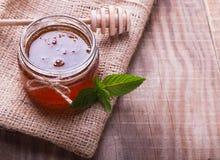 Miel en un tarro, una cuchara de la miel y hojas de menta de cristal en el de madera Imagen de archivo