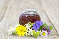 Miel en un tarro y flores Imagenes de archivo