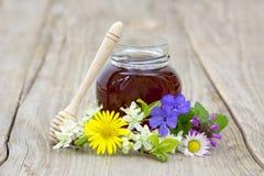 Miel en un tarro y flores Imagen de archivo libre de regalías