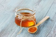Miel en una cuchara y un tarro de madera Foto de archivo libre de regalías