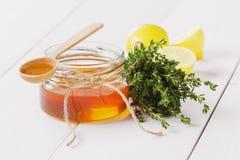 Miel en una cuchara y un tarro de madera Fotos de archivo
