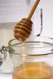 Miel en verre avec des bâtons Lizenzfreie Stockfotos