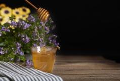 Miel en vidrio con la abeja Foto de archivo libre de regalías