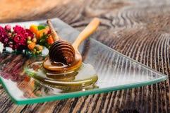 Miel et fleurs sur le plat en verre Images stock