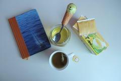 Miel et thé sur un bureau blanc Image libre de droits