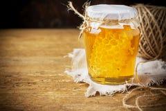 Miel floral fresca con el panal en un pequeño vidrio Imagen de archivo