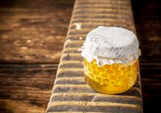 Miel floral fresca con el panal en un pequeño vidrio Imágenes de archivo libres de regalías