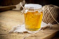 Miel floral fresca con el panal en un pequeño vidrio Fotos de archivo libres de regalías