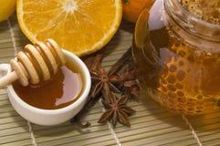 Miel frais avec le nid d'abeilles, les épices et les fruits Photos stock