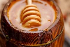 Miel frais délicieux dans un barillet et un bâton en bois immergés dans lui photos libres de droits