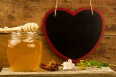 Miel fresca del tarro de cristal con el drizzler, canela, flores en fondo de madera Fotografía de archivo libre de regalías