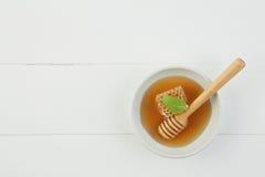 Miel fresca en la placa con el panal y cazo en la madera blanca Imagenes de archivo