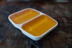 Miel líquida en una salsera blanca a partir de dos secciones En un vector de madera Imágenes de archivo libres de regalías