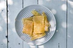 Miel ligera fresca de la abeja en pedazos de panales en una tabla rústica de madera blanca con el fondo de la falta de definición Fotografía de archivo libre de regalías