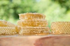 Miel ligera fresca de la abeja en pedazos de panales en una tabla rústica de madera blanca con el fondo de la falta de definición Fotos de archivo libres de regalías
