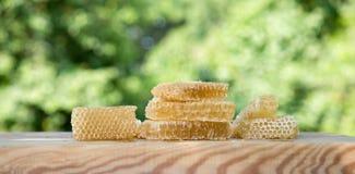 Miel ligera fresca de la abeja en pedazos de panales en una tabla rústica de madera blanca con el fondo de la falta de definición Fotografía de archivo