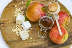Miel, manzanas y granadas en la cubierta de madera para la celebración de Rosh Hashana Imagen de archivo libre de regalías