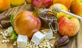 Miel, manzanas y granadas en la cubierta de madera para la celebración de Rosh Hashana Fotografía de archivo libre de regalías