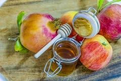 Miel, manzanas y granadas en la cubierta de madera para la celebración de Rosh Hashana Imágenes de archivo libres de regalías