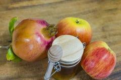 Miel, manzanas y granadas en la cubierta de madera para la celebración de Rosh Hashana Fotos de archivo libres de regalías