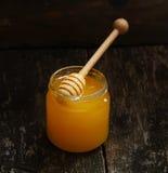 Miel natural en el pote con una cuchara especial para la miel en la tabla de madera rústica del vintage Fotos de archivo libres de regalías