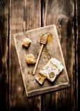 Miel natural en panales con una cuchara en el tablero Fotos de archivo