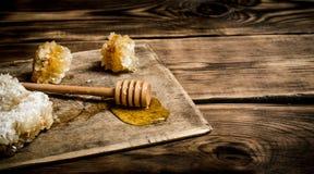 Miel natural en panales con una cuchara en el tablero Fotos de archivo libres de regalías