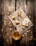 Miel natural en panales con una cuchara en el tablero Fotografía de archivo libre de regalías