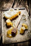 Miel natural en panales con una cuchara en el tablero Imagen de archivo