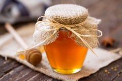 Miel natural miel fresca en el fondo de cristal del tarro Fotografía de archivo libre de regalías