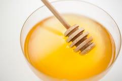 Miel naturel avec une cuillère en bois sur un fond blanc Photos stock