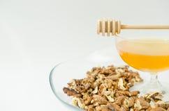 Miel naturel avec une cuillère en bois sur un fond blanc image stock