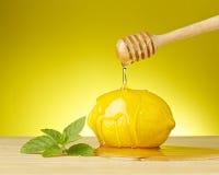 Miel orgánica de goteo con el limón y la menta en fondo amarillo Imagen de archivo