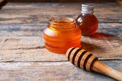 Miel orgánica en la tabla de madera fotos de archivo