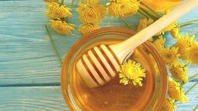 Miel, postre natural de la flor del crisantemo en el fondo de madera, cámara lenta almacen de metraje de vídeo
