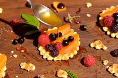 Miel que fluye abajo de la cuchara en la galleta con las frutas y las bayas Imagen de archivo libre de regalías