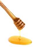Miel que fluye abajo de un cazo de madera de la miel Foto de archivo