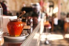 Miel sabrosa en un tarro de cristal con una cuchara de madera especial en el primero plano en un café con un fondo borroso Imagen de archivo libre de regalías