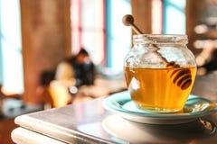 Miel sabrosa en un tarro de cristal con una cuchara de madera especial en el primero plano en un café con un fondo borroso Fotografía de archivo