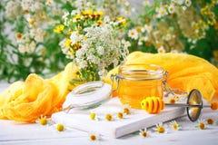 Miel sabrosa y sana en la tabla de madera blanca con las flores de la manzanilla fotos de archivo libres de regalías