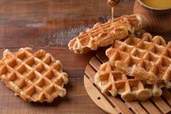 Miel versant sur les gaufres fraîches Petit déjeuner avec des gaufres photo stock