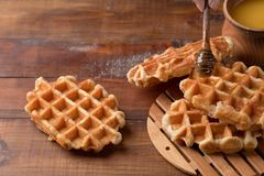 Miel versant sur les gaufres fraîches Petit déjeuner avec des gaufres images libres de droits