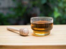 Miel y cazo de la miel en fondo de madera Imagen de archivo libre de regalías